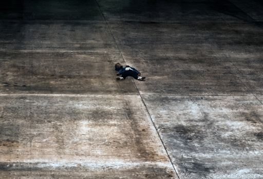 wide shot of person laid in star position on an expanse of conrete