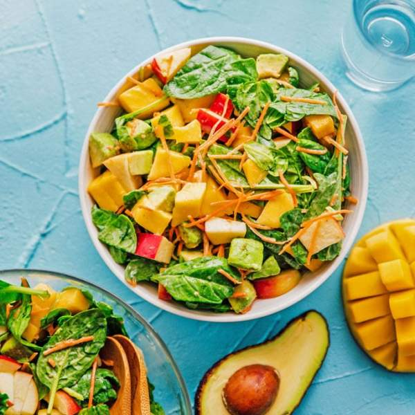 Salad with spinach, mango, carrots, and apple in a bowl on a blue background