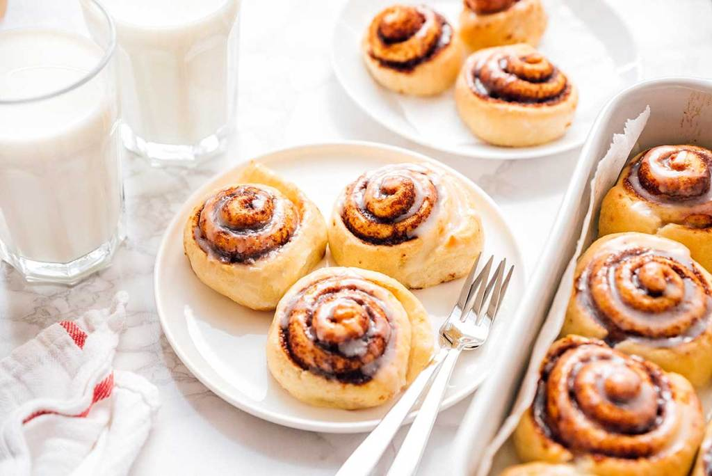 Cinnamon rolls with icing on a plate with marble background