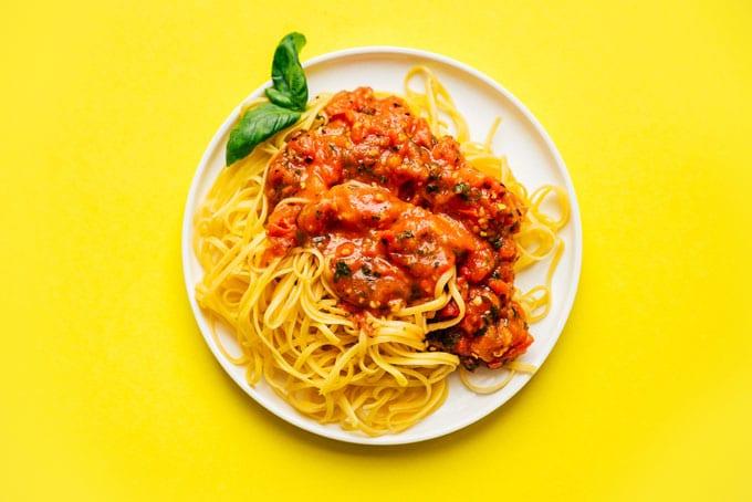 Chunky fresh marinara sauce on a plate of spaghetti
