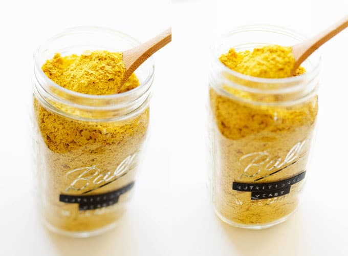 Jar of nutritional yeast on a white background with a spoon in it