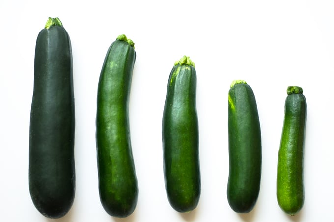 Zucchinis of different sizes on white background