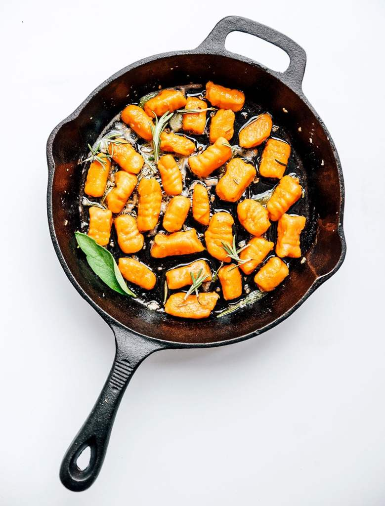 Sweet potato gnocchi in a skilley on a white background