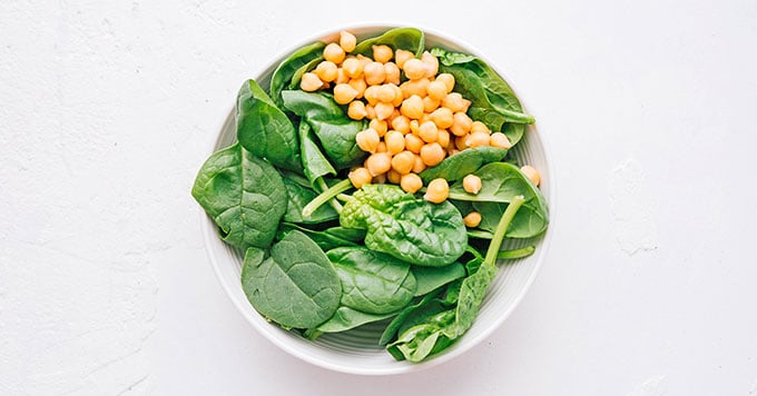 Chickpeas and spinach in a white bowl