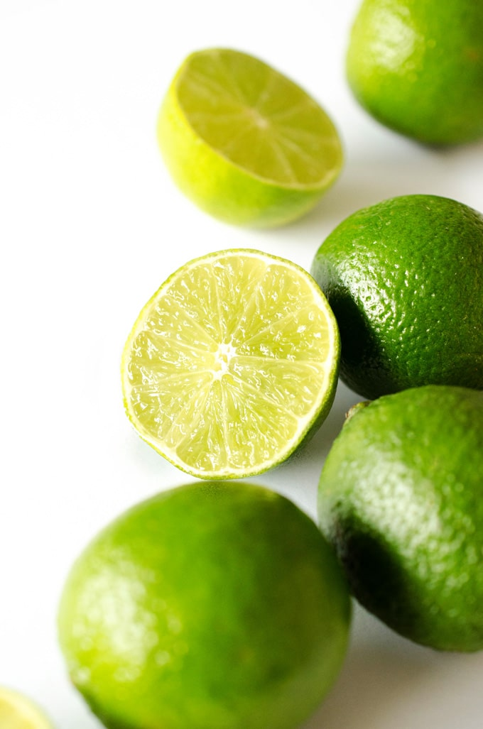 Close up photo of limes cut in half on a white background