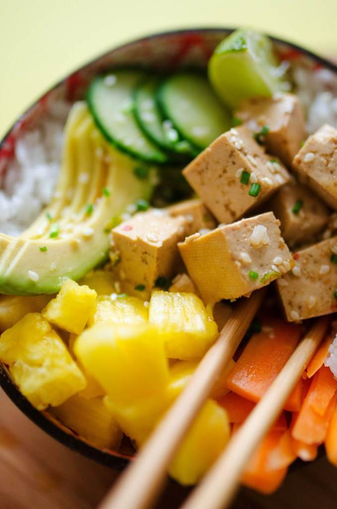 Vegan poke bowls with tofu, pineapple, avocado, and rice in a bowl