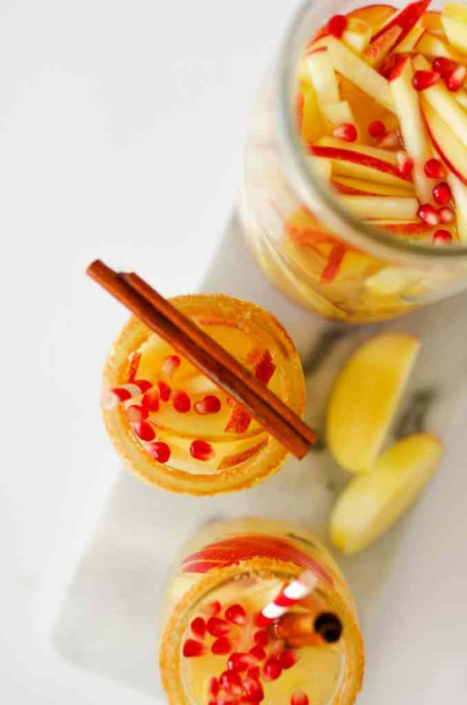Autumn Apple Sangria in a glass with cinnamon and apples from above