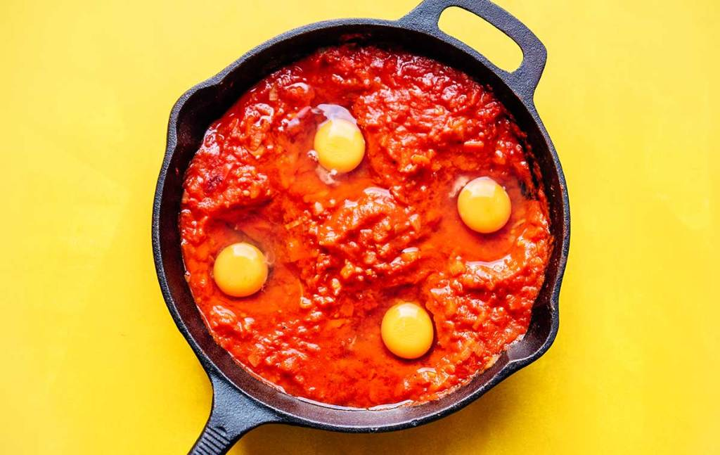 Raw eggs in tomato sauce for shakshuka in a cast iron skillet on a yellow background