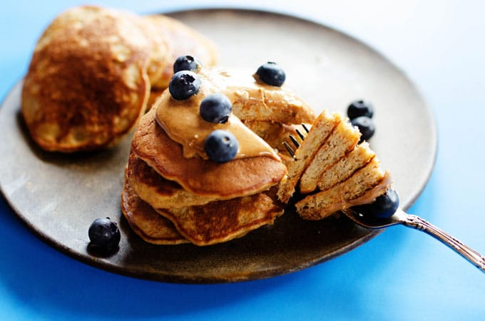 Paleo pancakes stacked with almond butter and blueberries