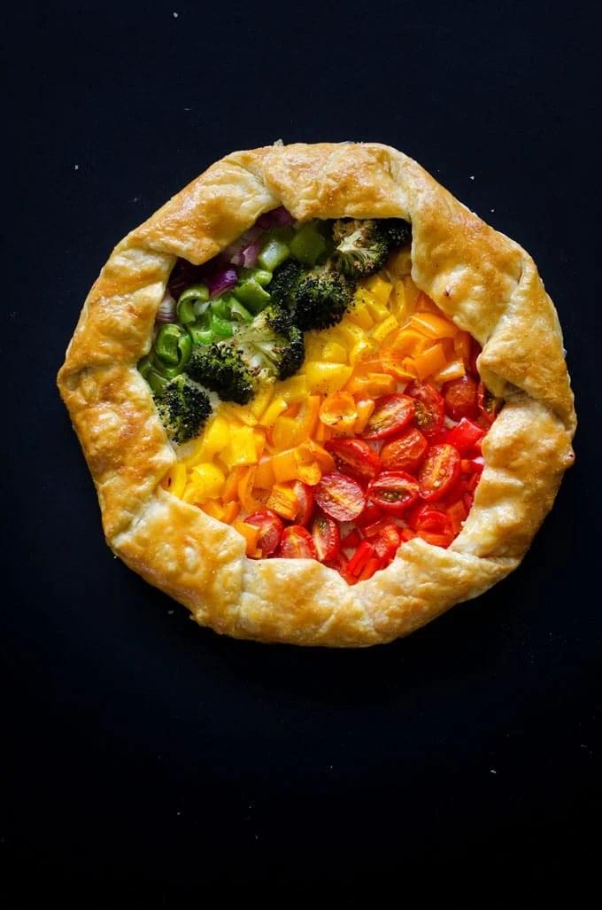 Rainbow savory vegetable tart on a black background