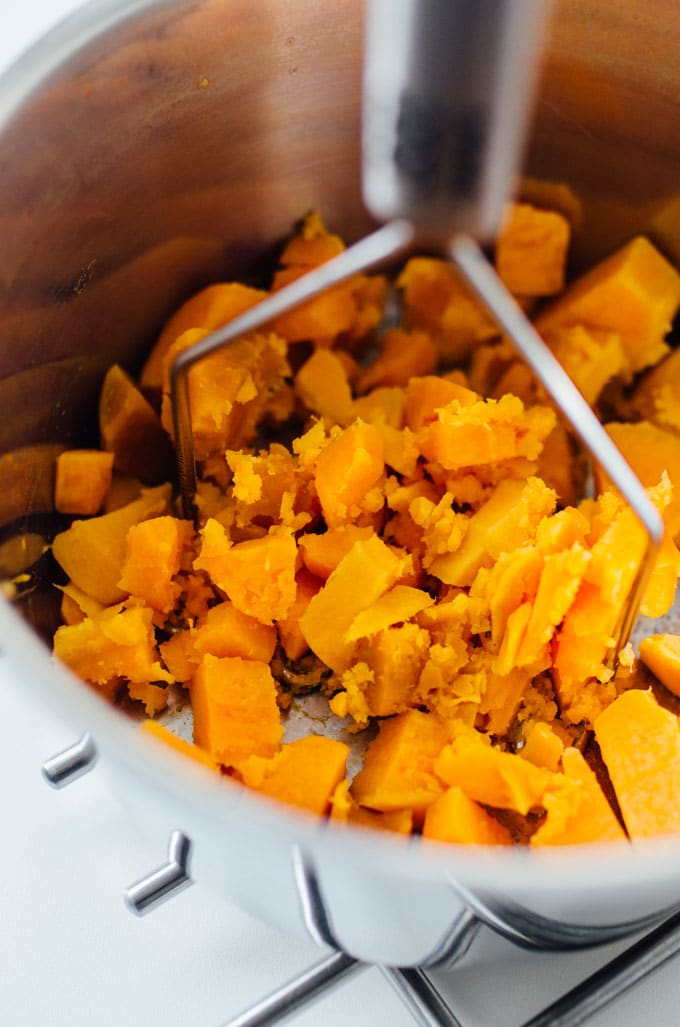 Mashing sweet potatoes in a bowl - Need a healthy cookie recipe that's just as moist and delicious as your old favorites? This Sweet Potato Cookie recipe with chocolate and oats has you covered.