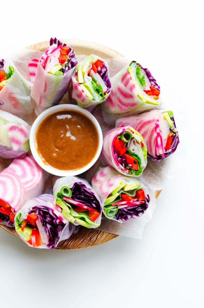 Spring rolls with heart shaped beets on a white plate with almond butter dipping sauce - Stuffed with fuchsia root vegetables, creamy avocado, and herbs then served with the most delicious almond butter sauce of your life, these vegan spring rolls are perfect for your healthy Valentine's Day dinner.
