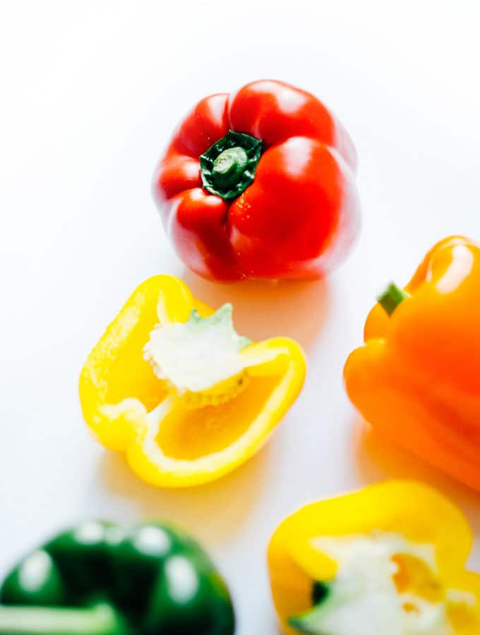Red, yellow, orange, and green bell peppers on a white background