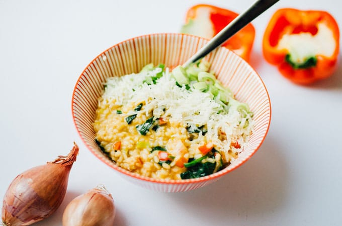 Bell pepper risotto in a striped bowl on a white background