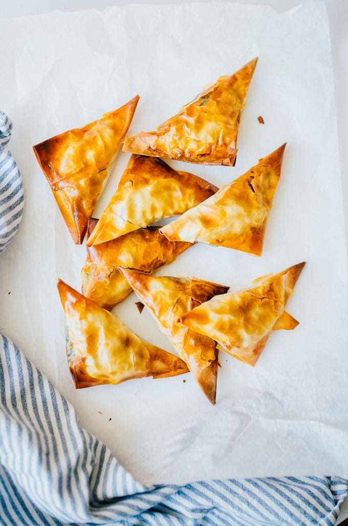 These Spanakopita Triangles are a simple appetizer jam-packed with feta and spinach, wrapped up in buttery, flaky phyllo crust.