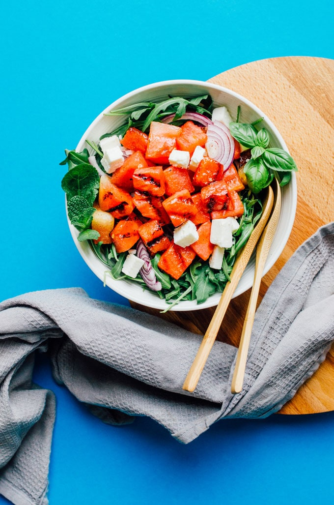 Grilled watermelon salad with arugula, feta cheese, and mint in a bowl on a blue background