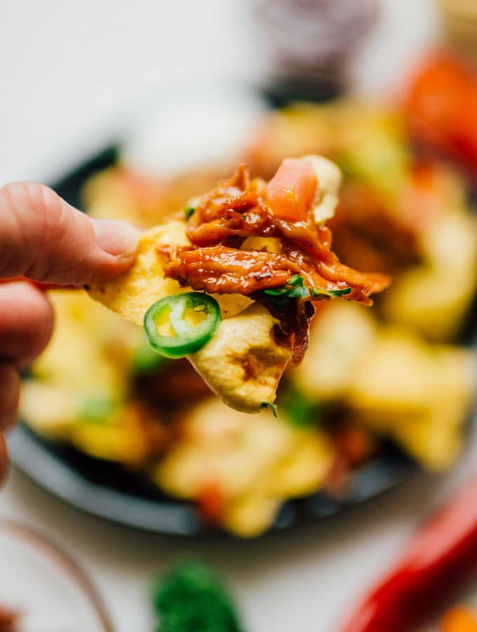 "Closeup of nacho chip in hand - These vegan nachos are piled high with easy mushroom BBQ ""pulled pork"" and a cashew-based queso cheese sauce that will knock your dairy-free socks off."
