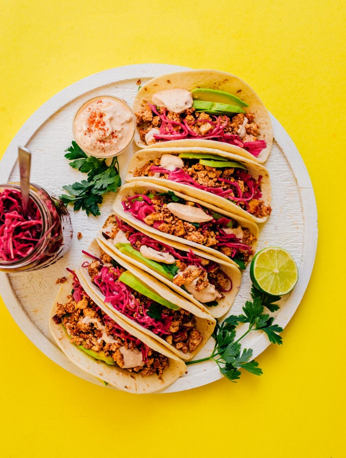 Soyrizo tacos with pickled red cabbage on a plate from overhead with a yellow background