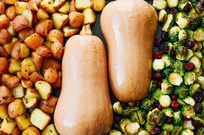 Butternut squash on a baking sheet with potatoes and brussels sprouts