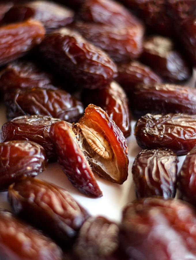 Close up photo of a date fruit cut in half with the seed showing