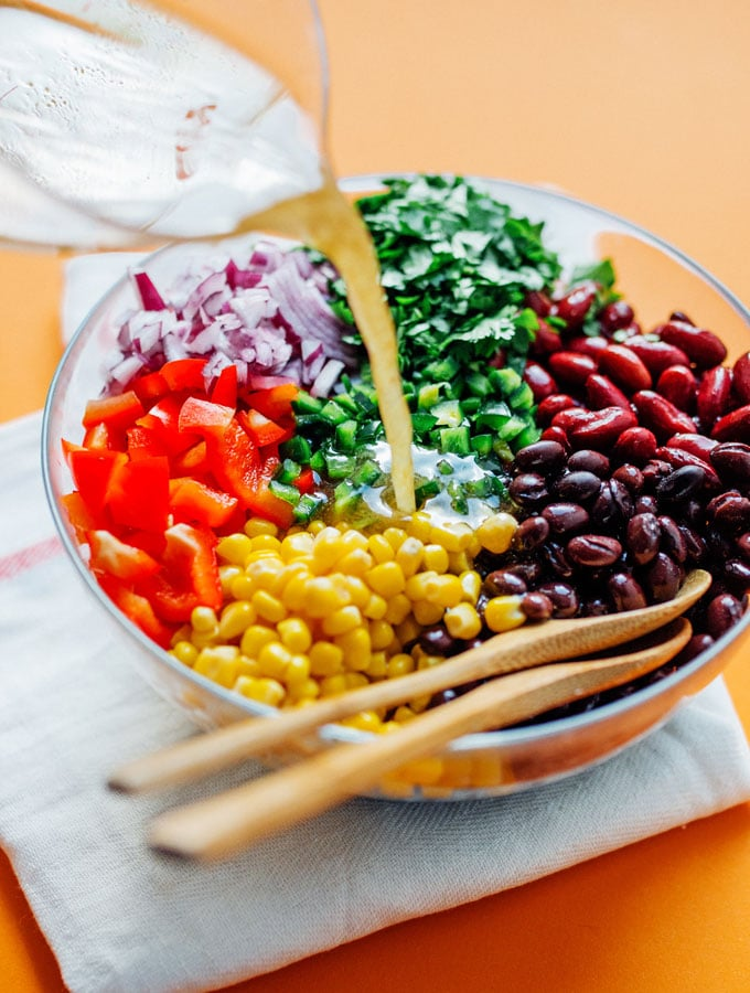 bean salad recipe in a bowl with dressing being poured in