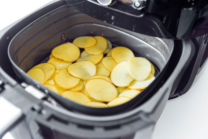 Potatoes in an air fryer - The ultimate guide on how to cook air fryer potatoes! How to make roasted potatoes, homemade French fries, and potato chips in your air fryer, using both white potatoes and sweet potatoes.