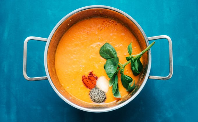 Fresh tomato soup in a pot with spices and basil