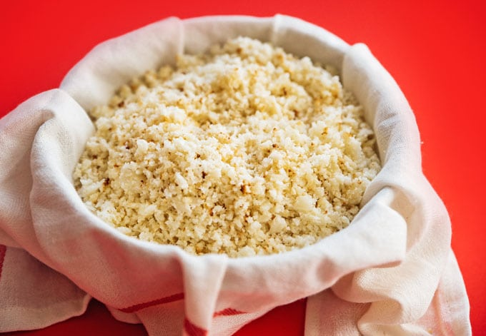 Ingredients to make cauliflower pizza crust recipe on red background