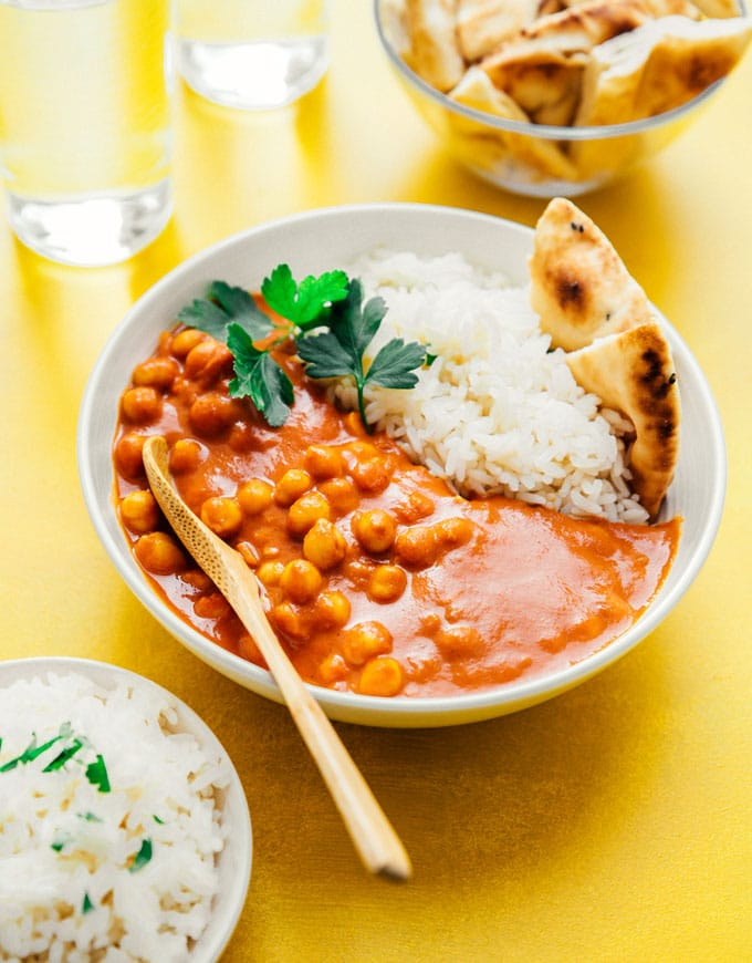 Vegan tikka masala with naan and rice in a white bowl