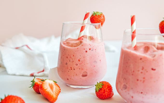 Strawberry smoothie in a glass with a striped straw