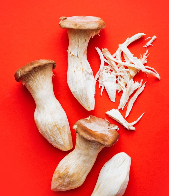 Shredded king oyster mushrooms on a red background