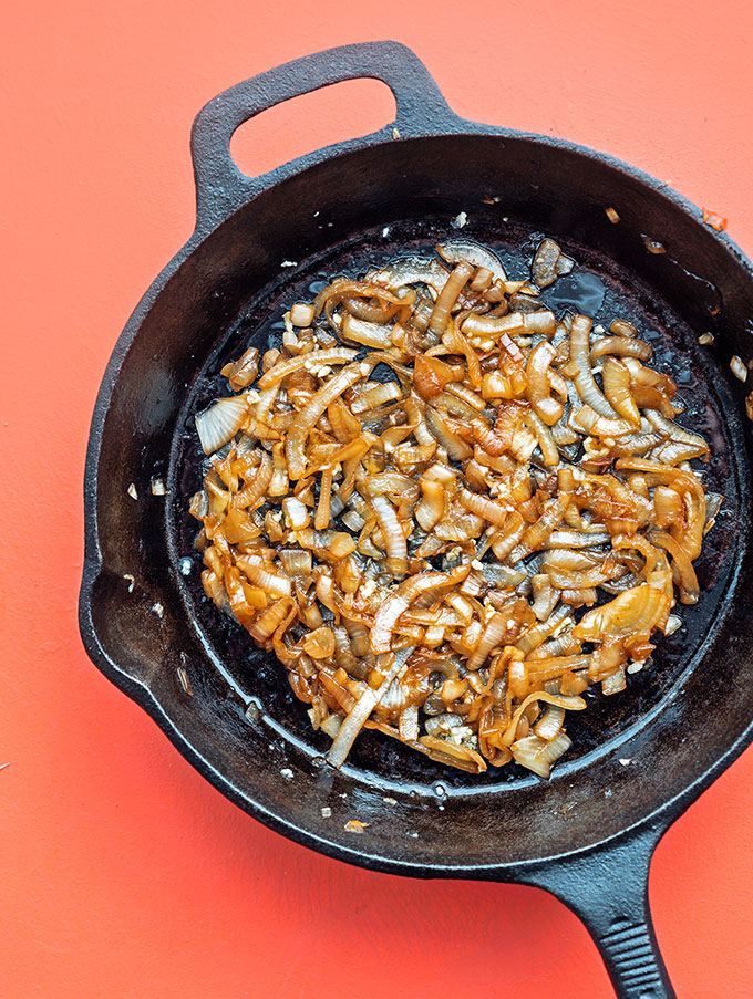Caramelized onions in a cast iron skillet on pink background