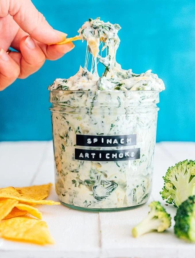 Spinach artichoke dip in a jar with a cheesy dip