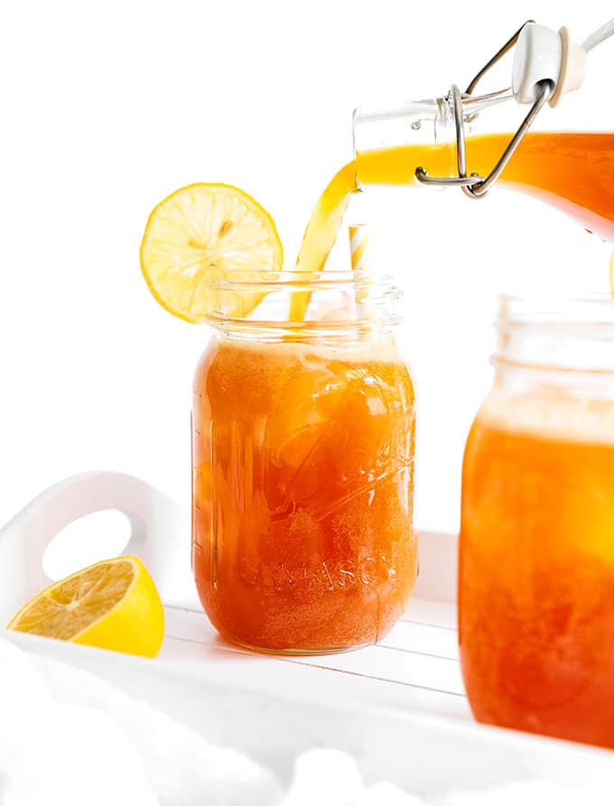 Lemon ginger kombucha in a mason jar on a white background