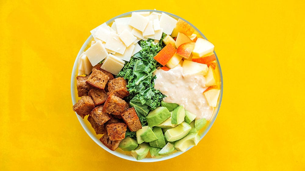 Ingredients to make kale salad in a bowl on yellow background