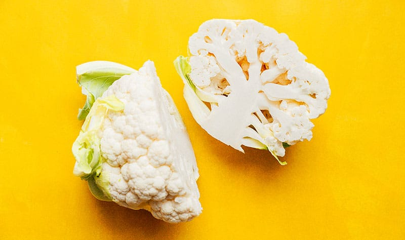 Cauliflower cut in half on a yellow background