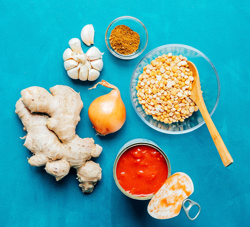 Garlic, ginger, onion, chana dal, diced tomatoes, and spices on a blue background