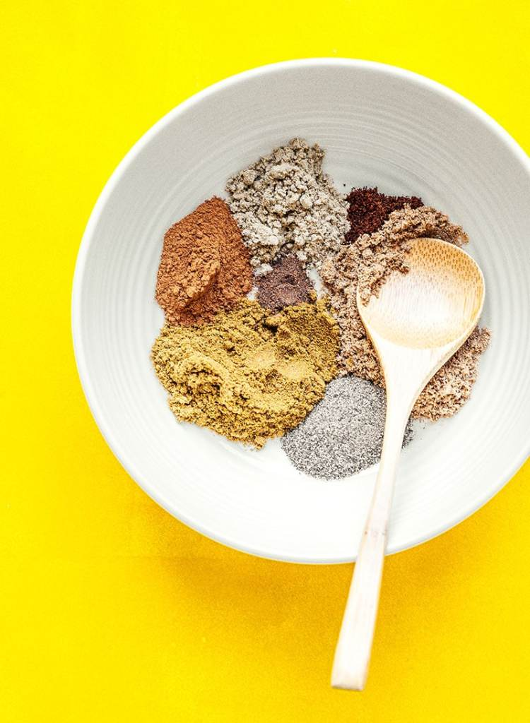 Spices to make homemade garama masala on a yellow background