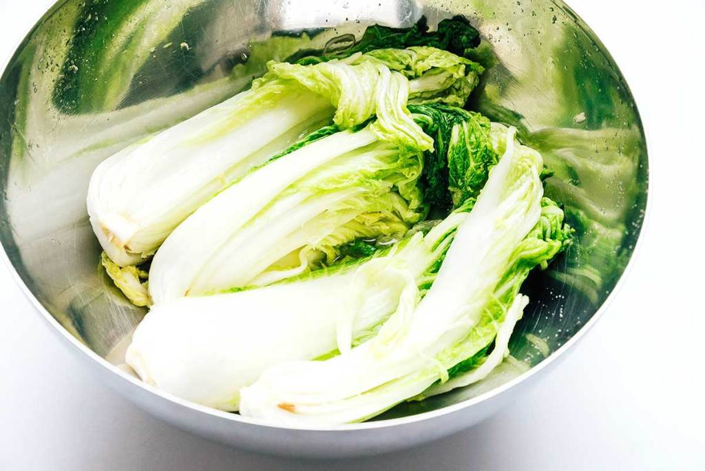 Wilted cabbage with salt in a bowl on white background