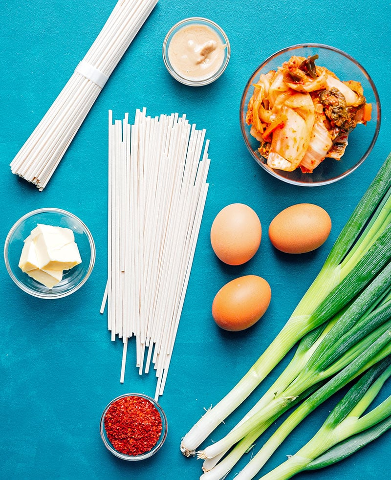 Birds eye view of kimchi udon noodle ingredients laid out on a blue background