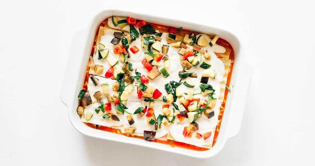 A casserole dish filled with marinara, mozzarella, lasagna noodles, bechamel, and vegetables