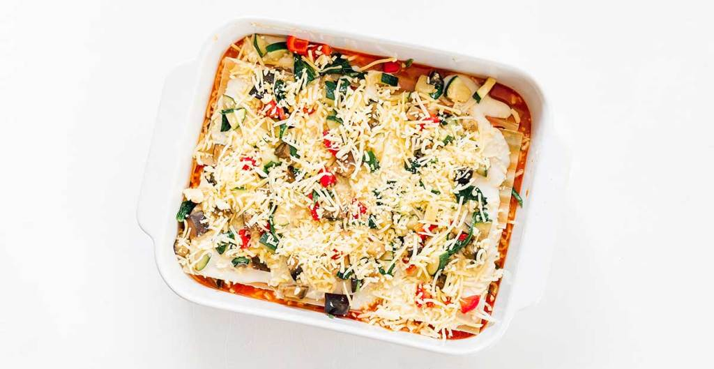 A casserole dish filled with marinara, lasagna noodles, bechamel, veggies, and mozzarella