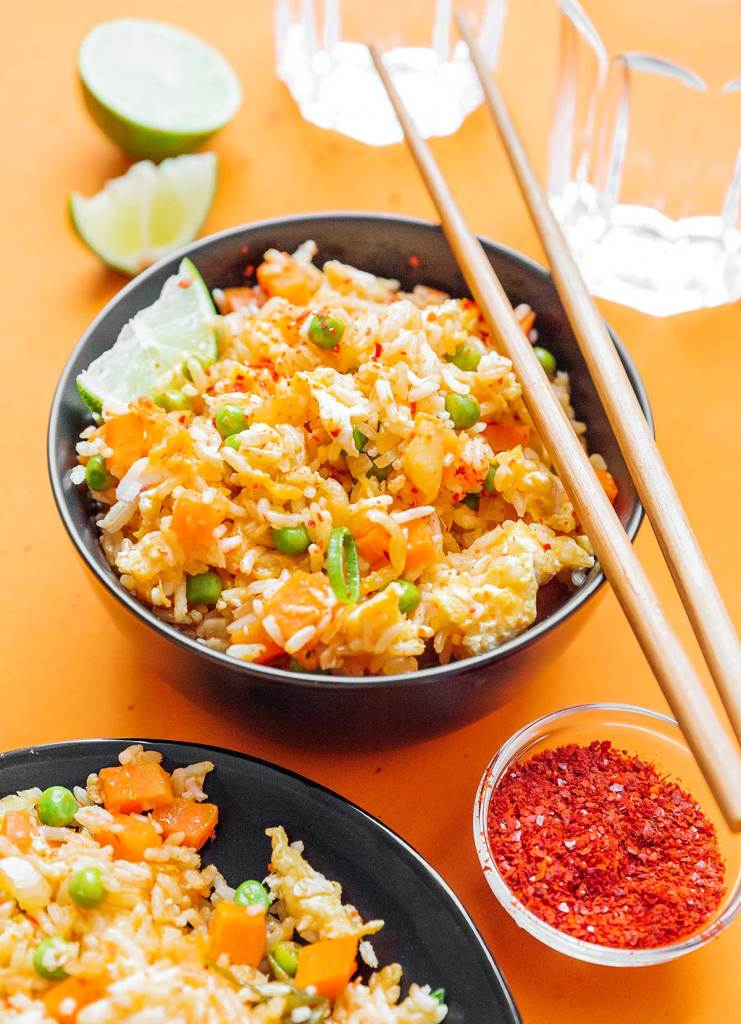 Detailed image of a bowl of kimchi fried rice on an orange background