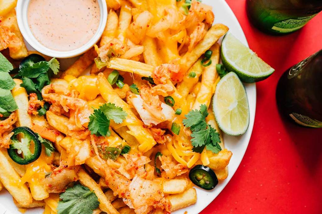 Close up shot of kimchi fries, sauce, lime slices, and toppings on a plate on a red background