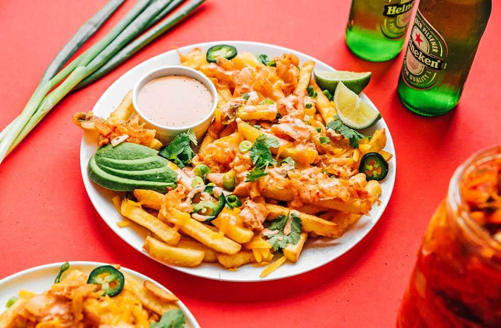 Kimchi fries, sauce, avocado slices, lime slices, and toppings on a plate on a red background