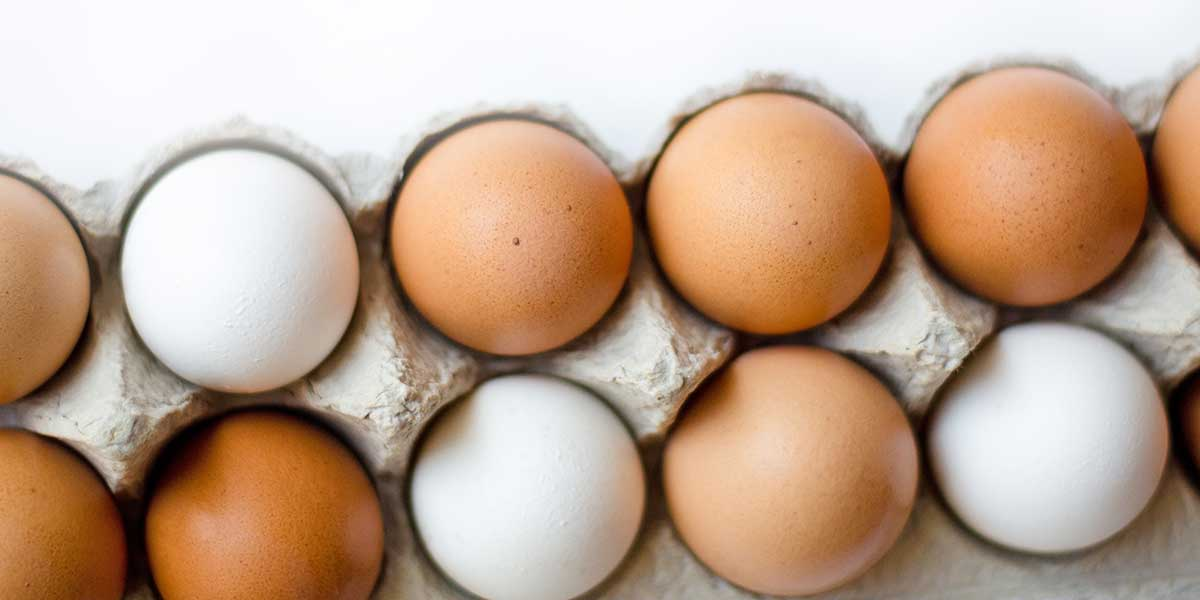 Brown and white eggs in a carton