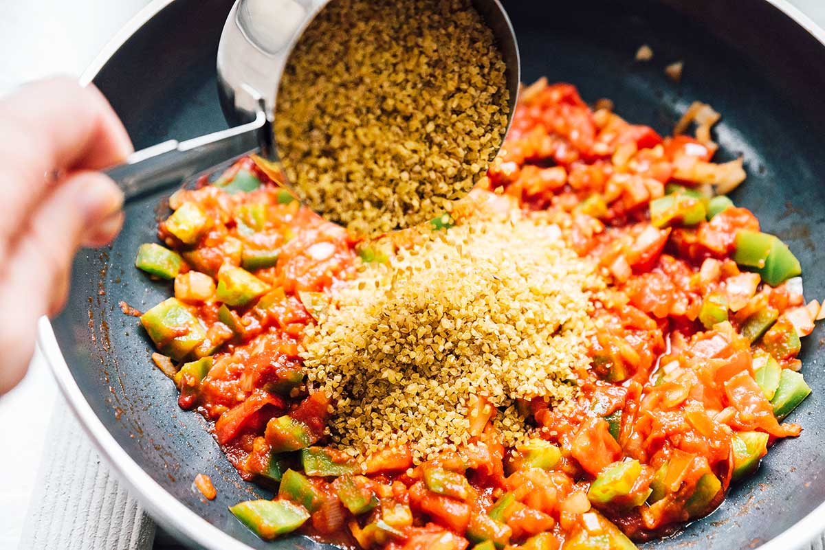 Adding bulgur to a pan filled with chopped veggies and diced tomatoes.
