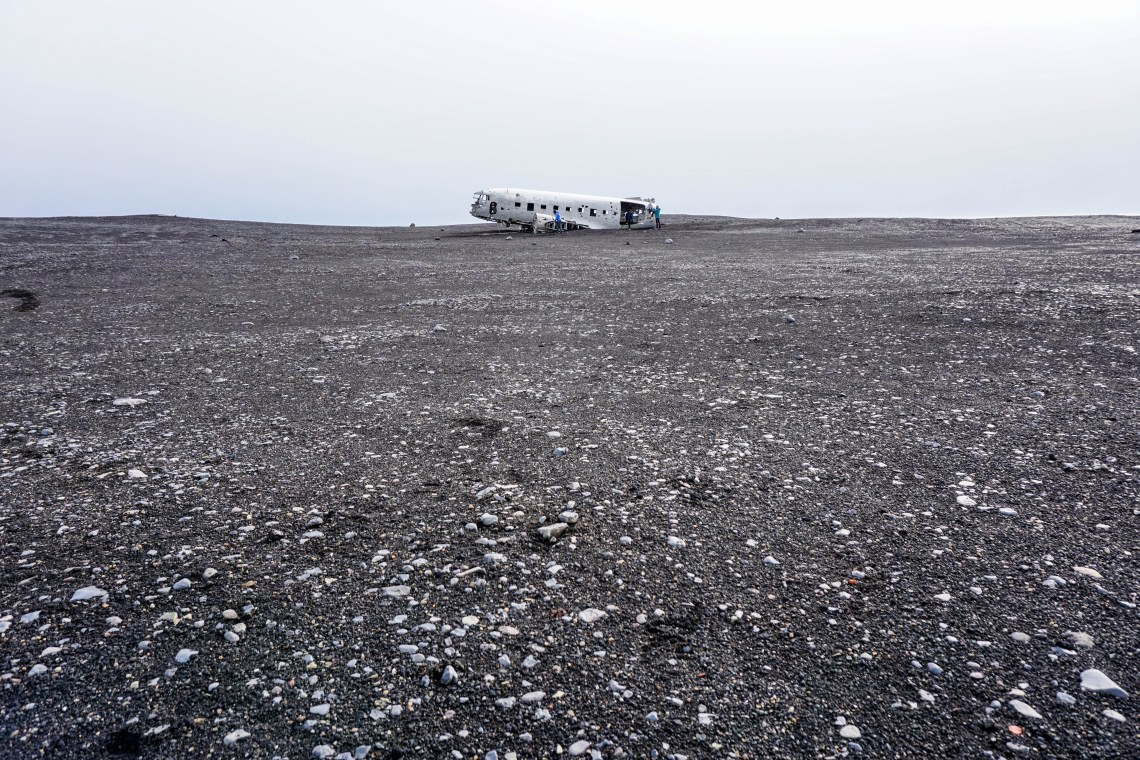 The first glimpse of the amazing yet eerie plane wreck on Solheimasandur black sand beach in South Iceland | Life With a View