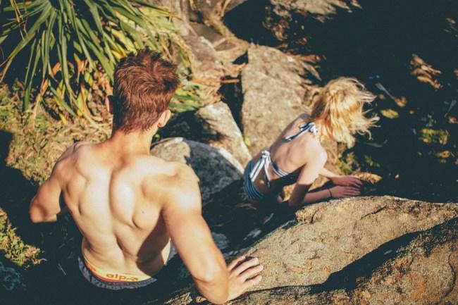man and woman rock climbing hiking couple