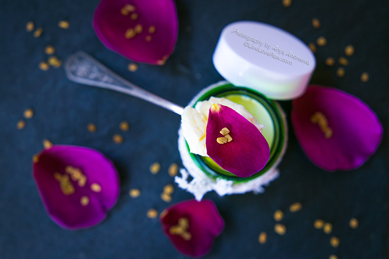 Natural organic face cream in a green bottle with rose petals